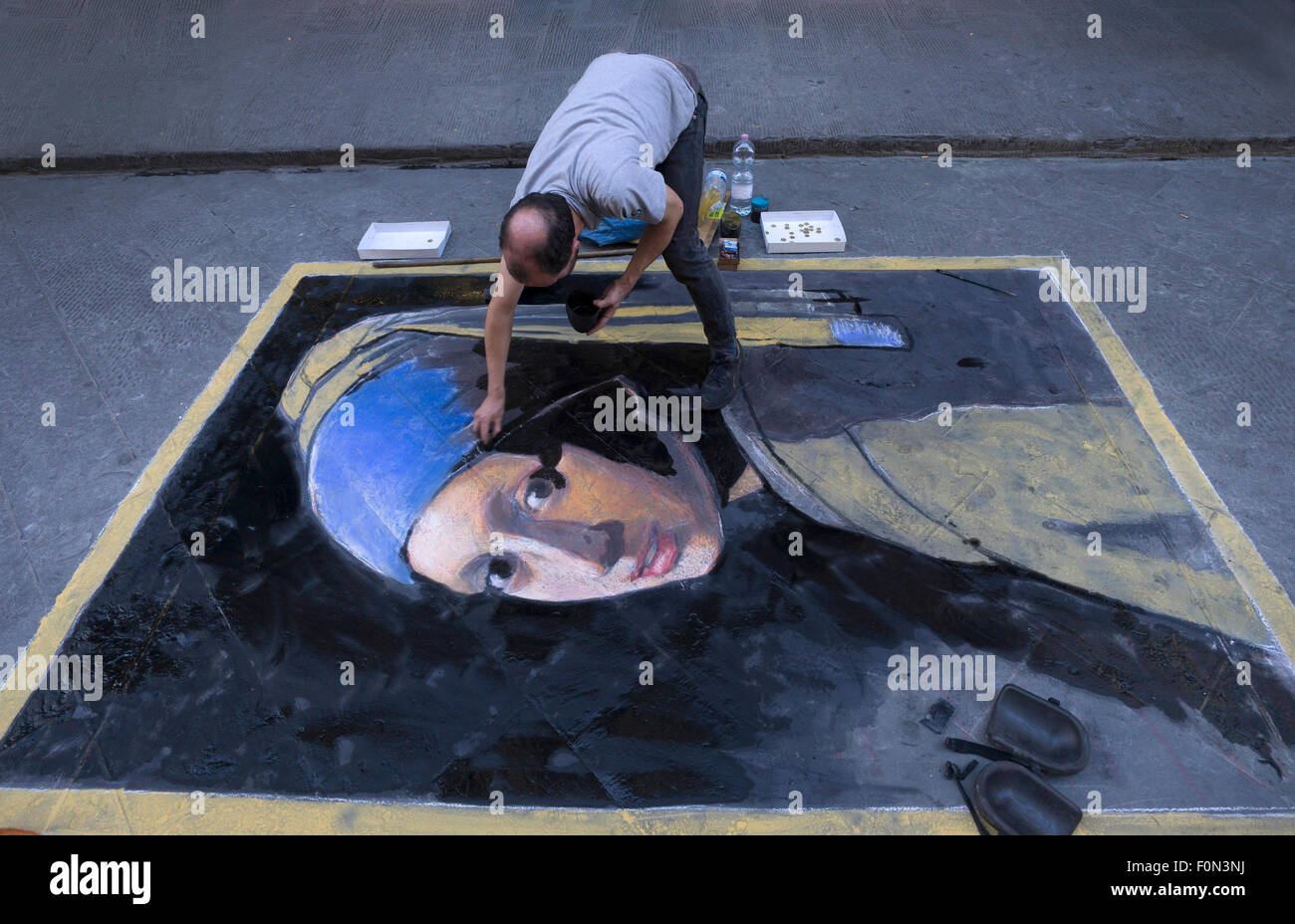 Man working on street chalk drawing of Vermeer woman with pearl earing. - Stock Image