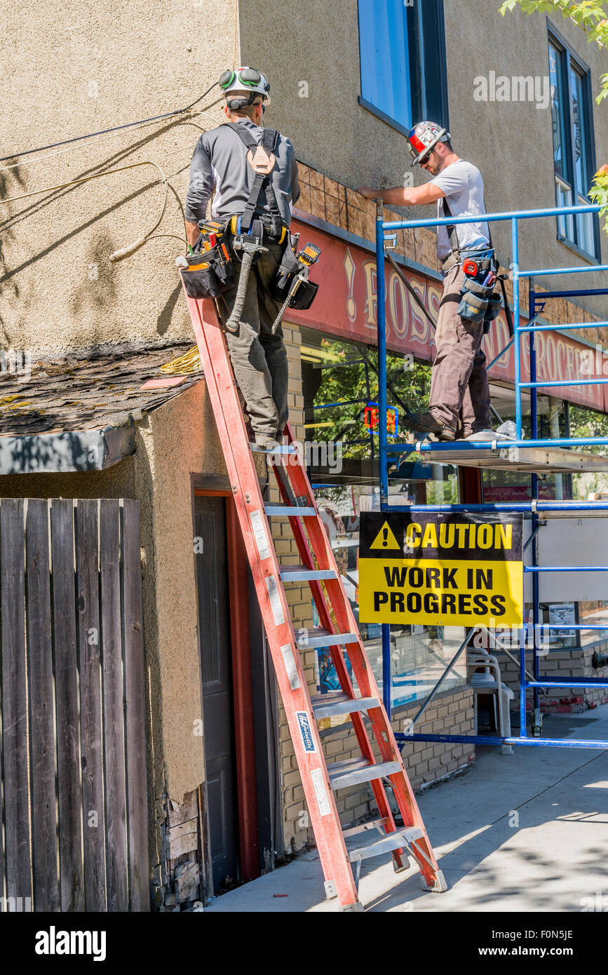 Men at work on scaffold and ladder, Rossland, British Columbia, Canada - Stock Image