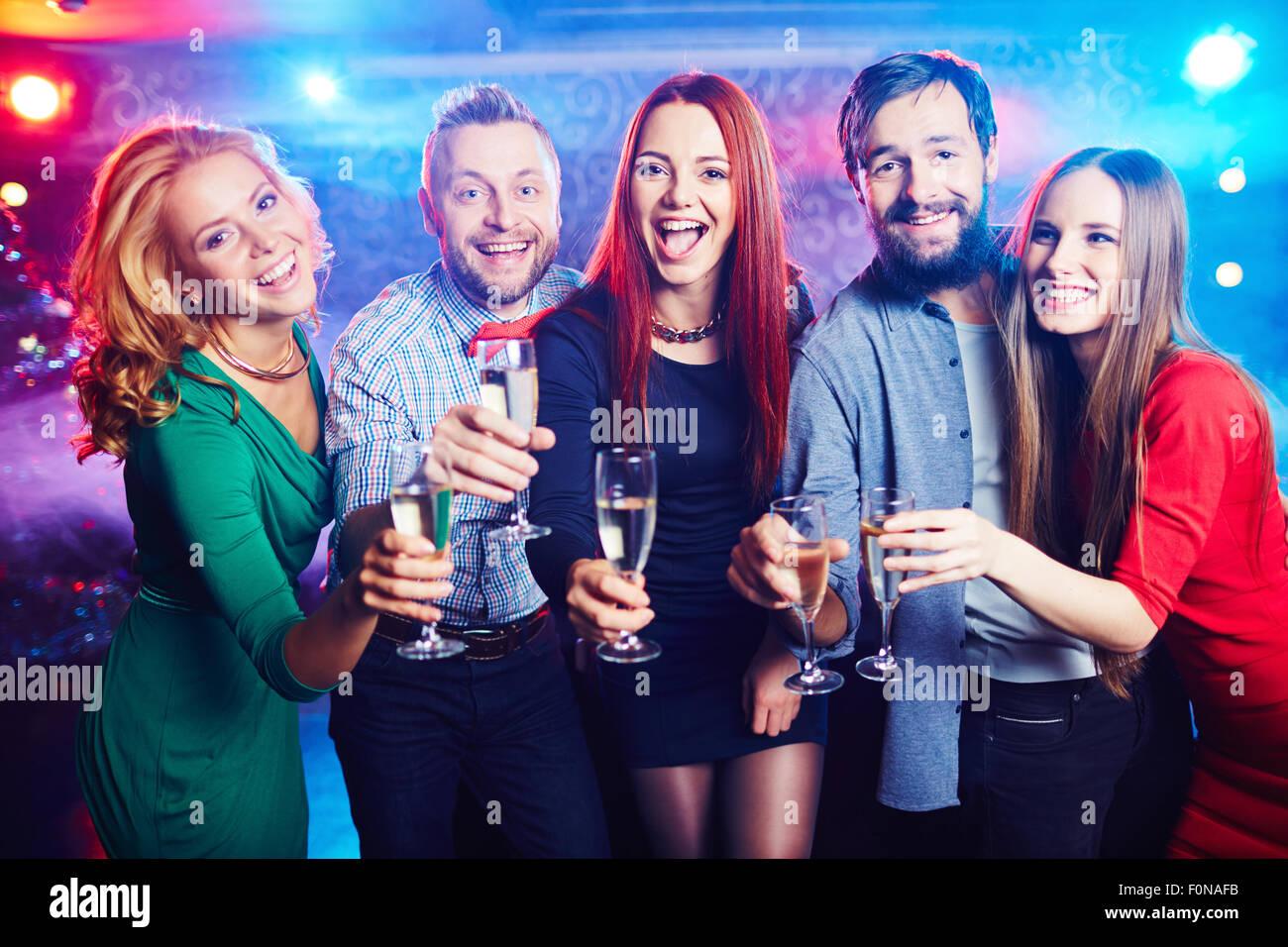 Joyful friends drinking wine at nightclub Stock Photo