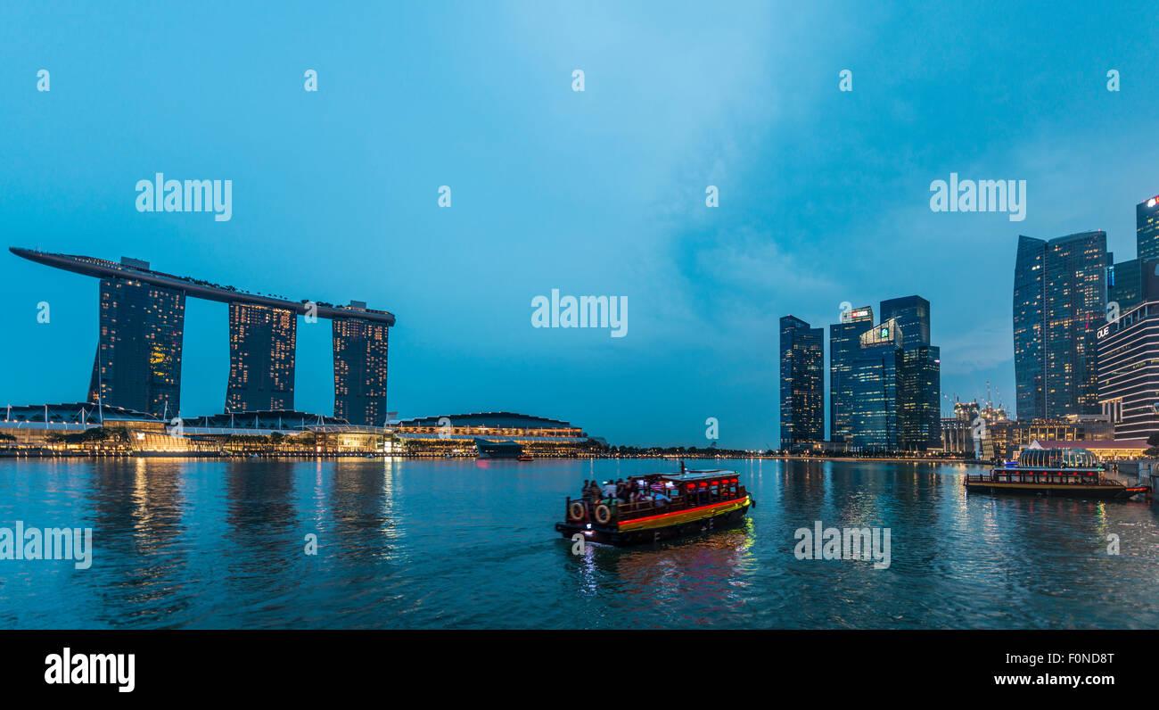 Boat on the Singapore River at dusk, Marina Bay Sands Hotel and Finance District behind, dusk, Marina Bay, Singapore - Stock Image