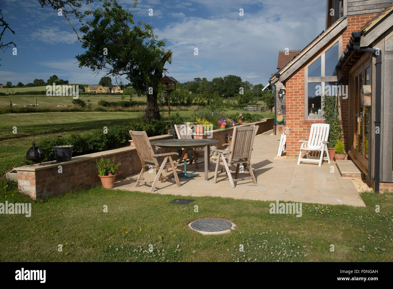 Empty teak chairs and table on patio of new ecohouse UK - Stock Image