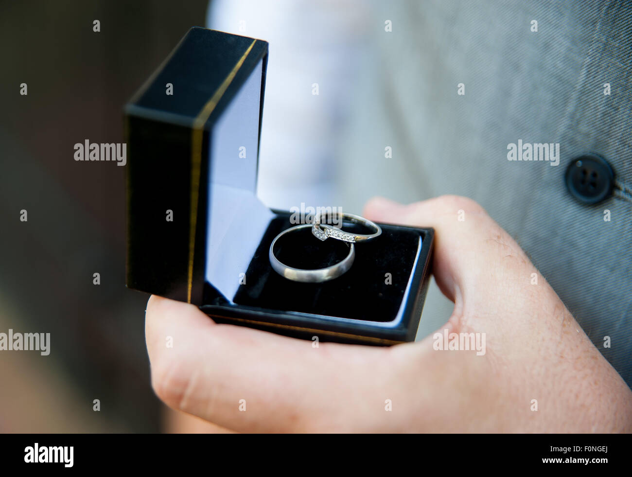 A best man at a wedding clutches firmly onto the wedding ring box before the ceremony. - Stock Image