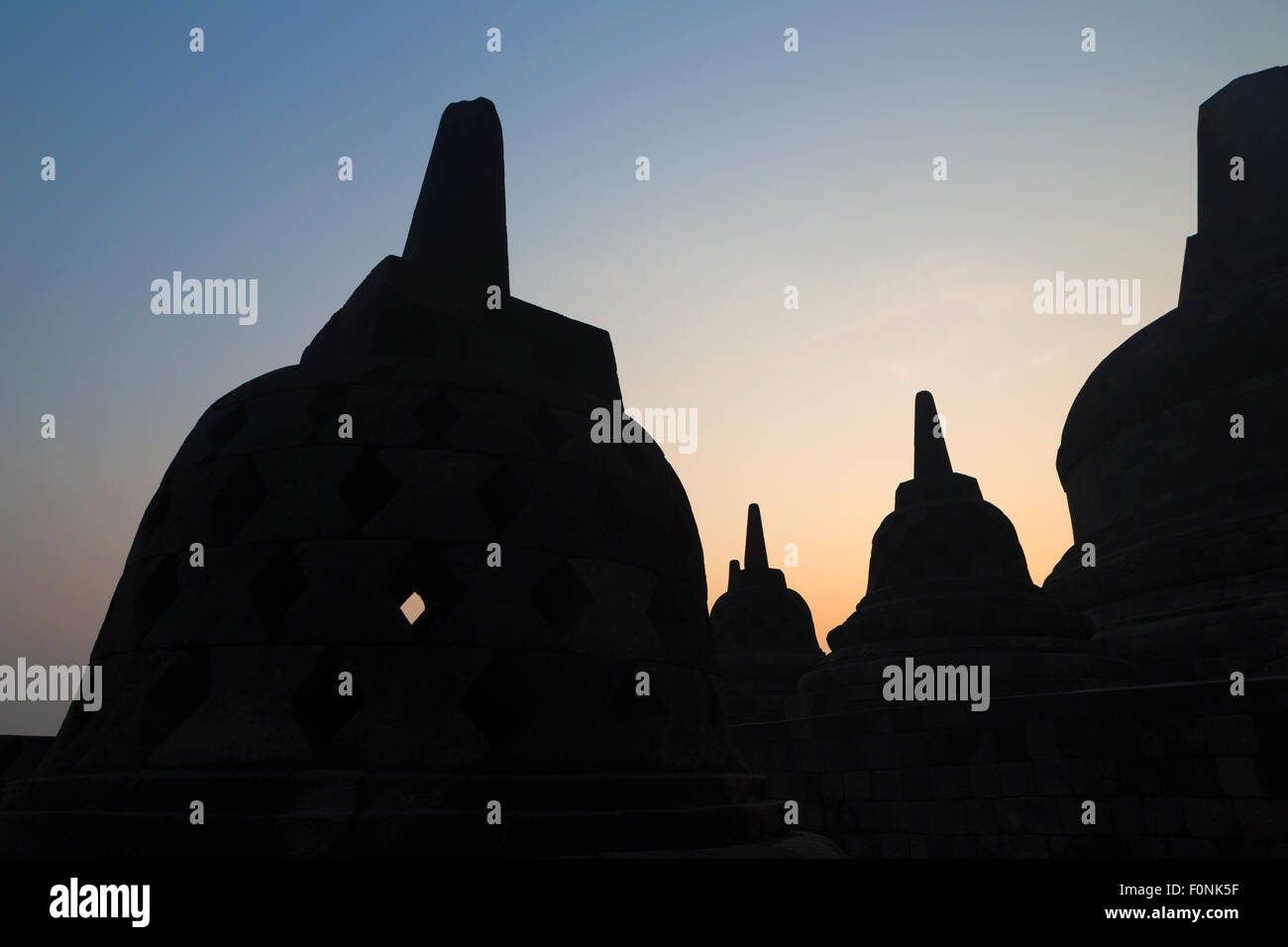 Silhouette's of Stupa's at sunrise at the Unesco world heritage site the Borobudur temple on Java, Indonesia, - Stock Image