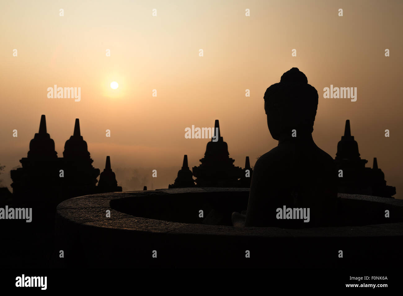 Silhouettes of a Buddha statue at the Unesco world heritage site the Borobudur temple at dawn on the island of Java, - Stock Image