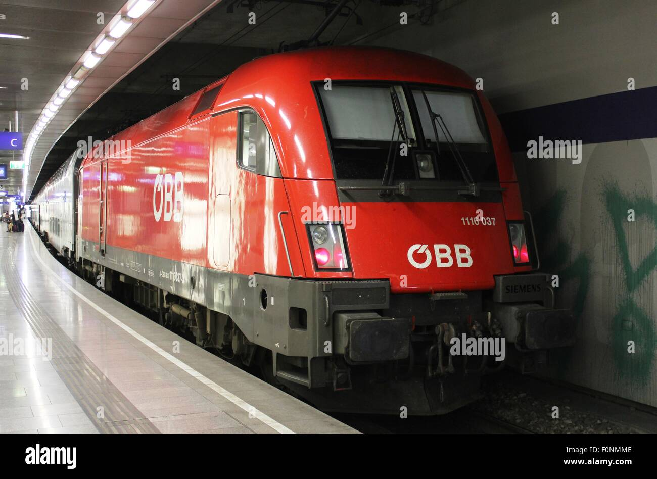Red electric locomotive in OBB livery, with passenger train at a platform in Vienna Mitte railway station in Austria. - Stock Image