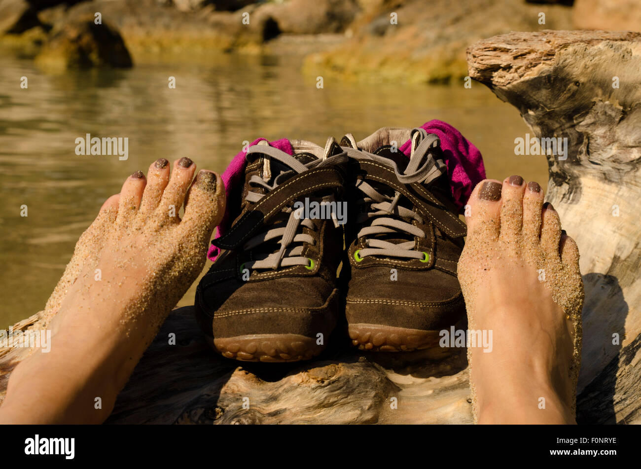 Shoes and bare feet on the beach - Stock Image