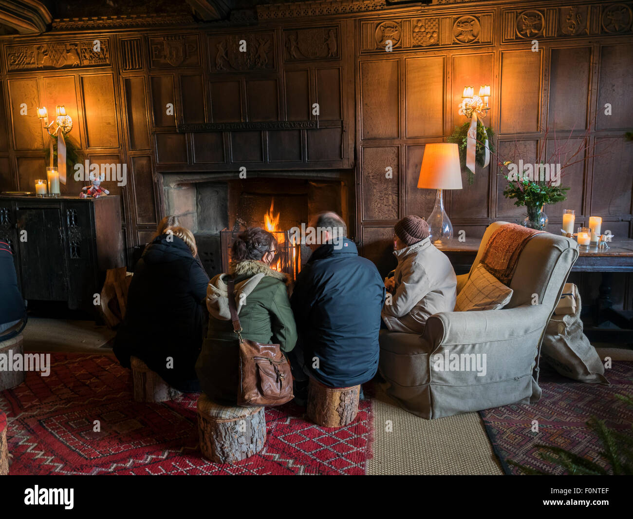 Family sitting round open fire Tudor Christmas in Haddon Hall in Derbyshire Peak District England - Stock Image