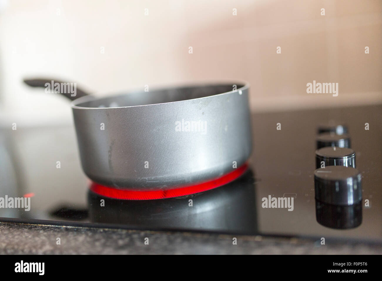pan of boiling water on an electric hob - Stock Image