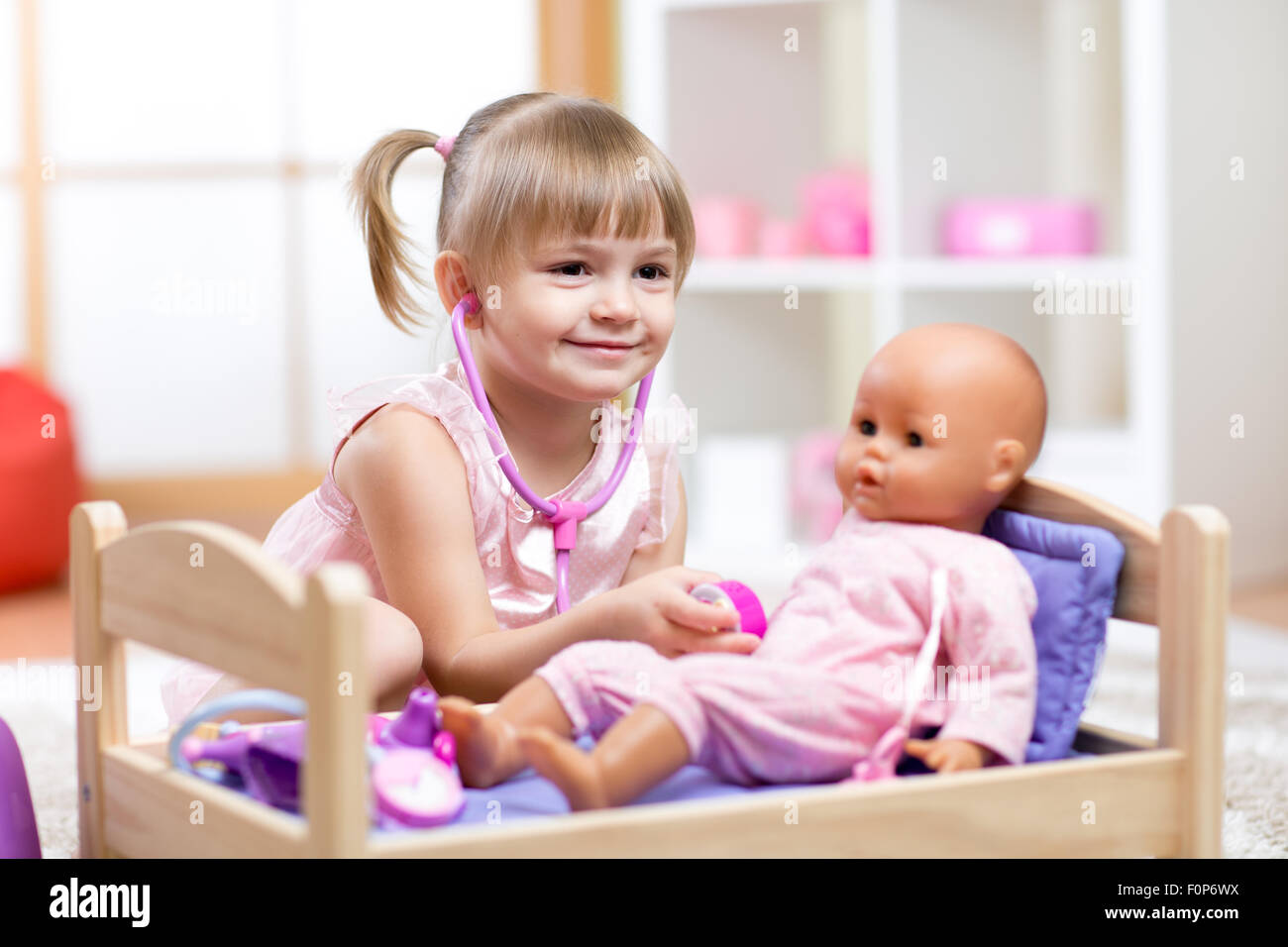 Child Playing Doctor with doll Toy - Stock Image