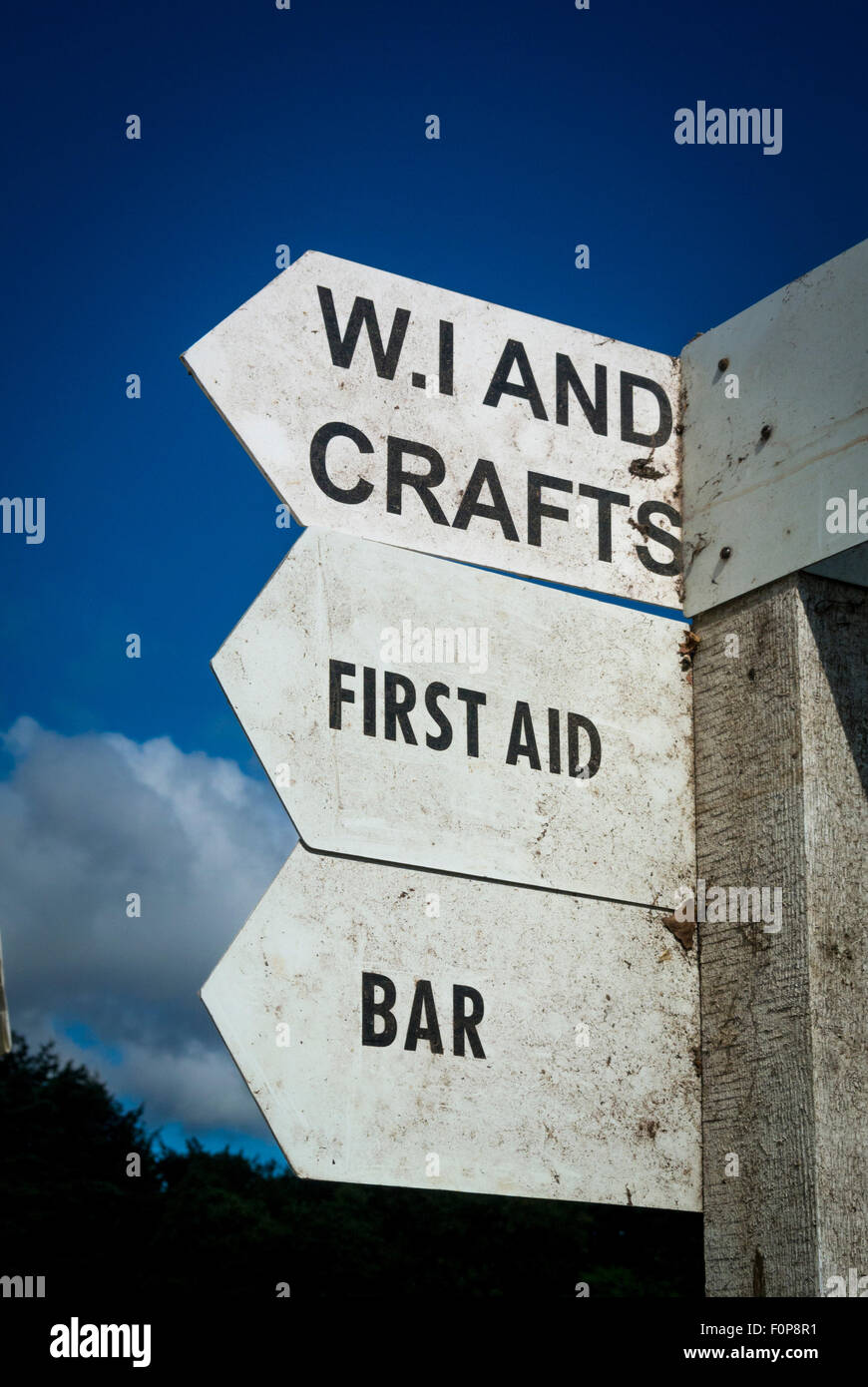 Signpost at local country show giving directions to WI and Crafts, First Aid and Bar. - Stock Image