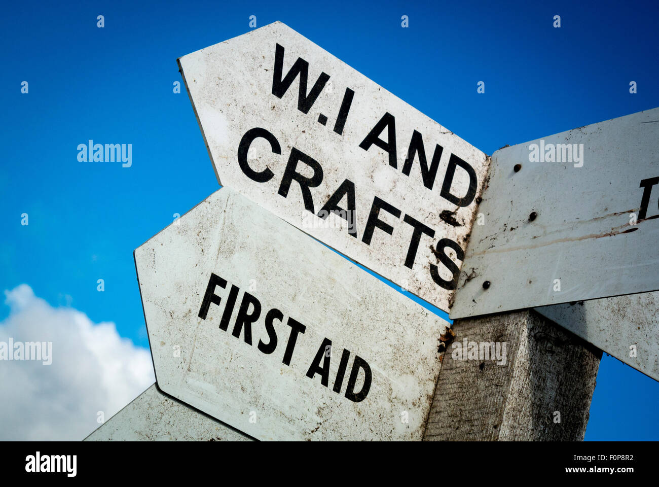 Signpost at local country show giving directions to WI and Crafts and First Aid. - Stock Image