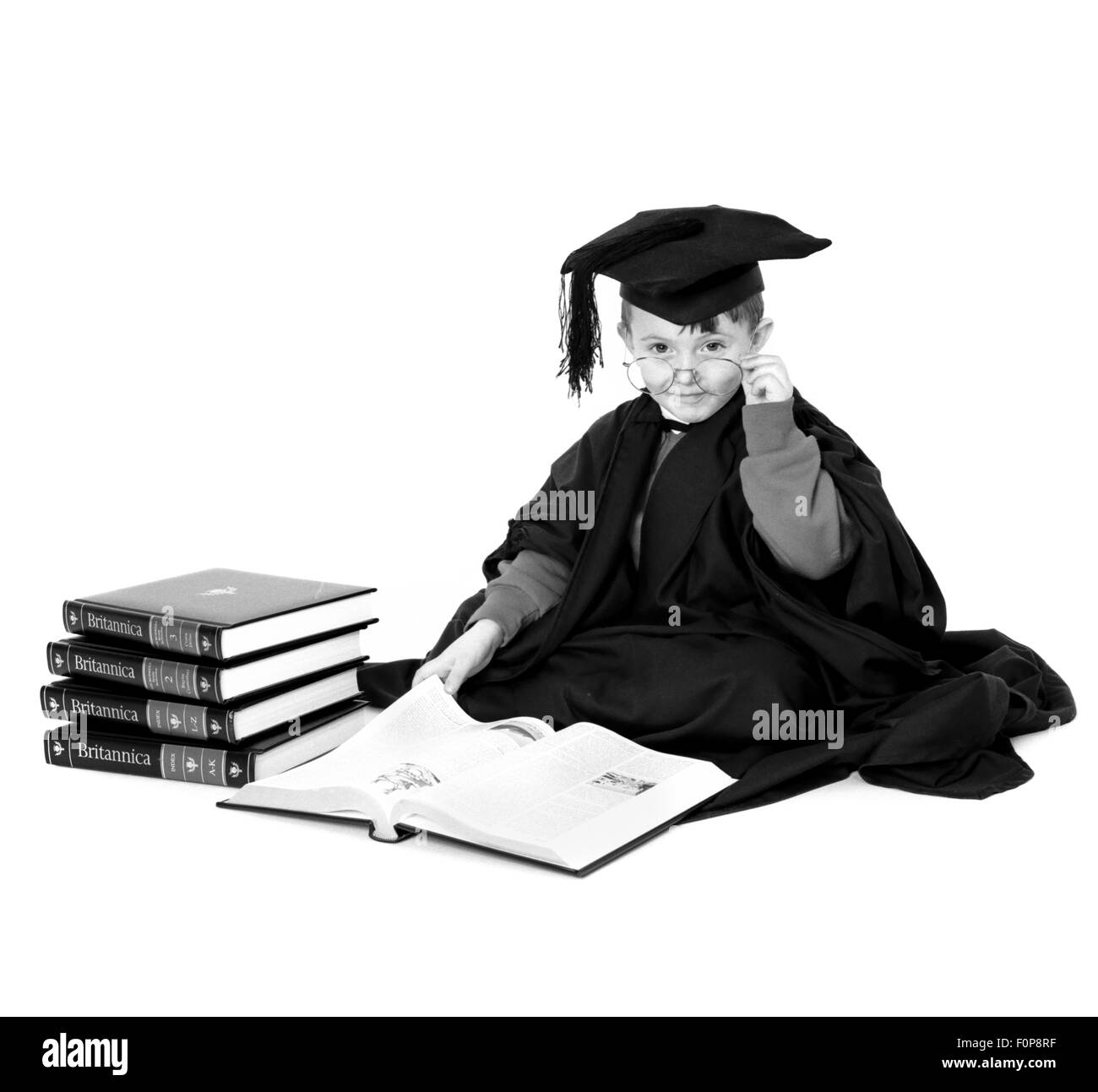 Young boy dressed in mortar board and gown reading Encyclopaedia Britannica - Stock Image