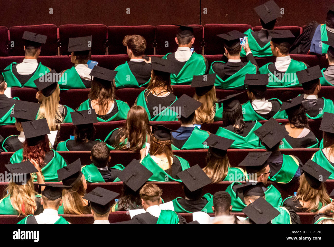 Rear view of Graduates waiting for presentation of degree certificates on Graduation Day - Stock Image