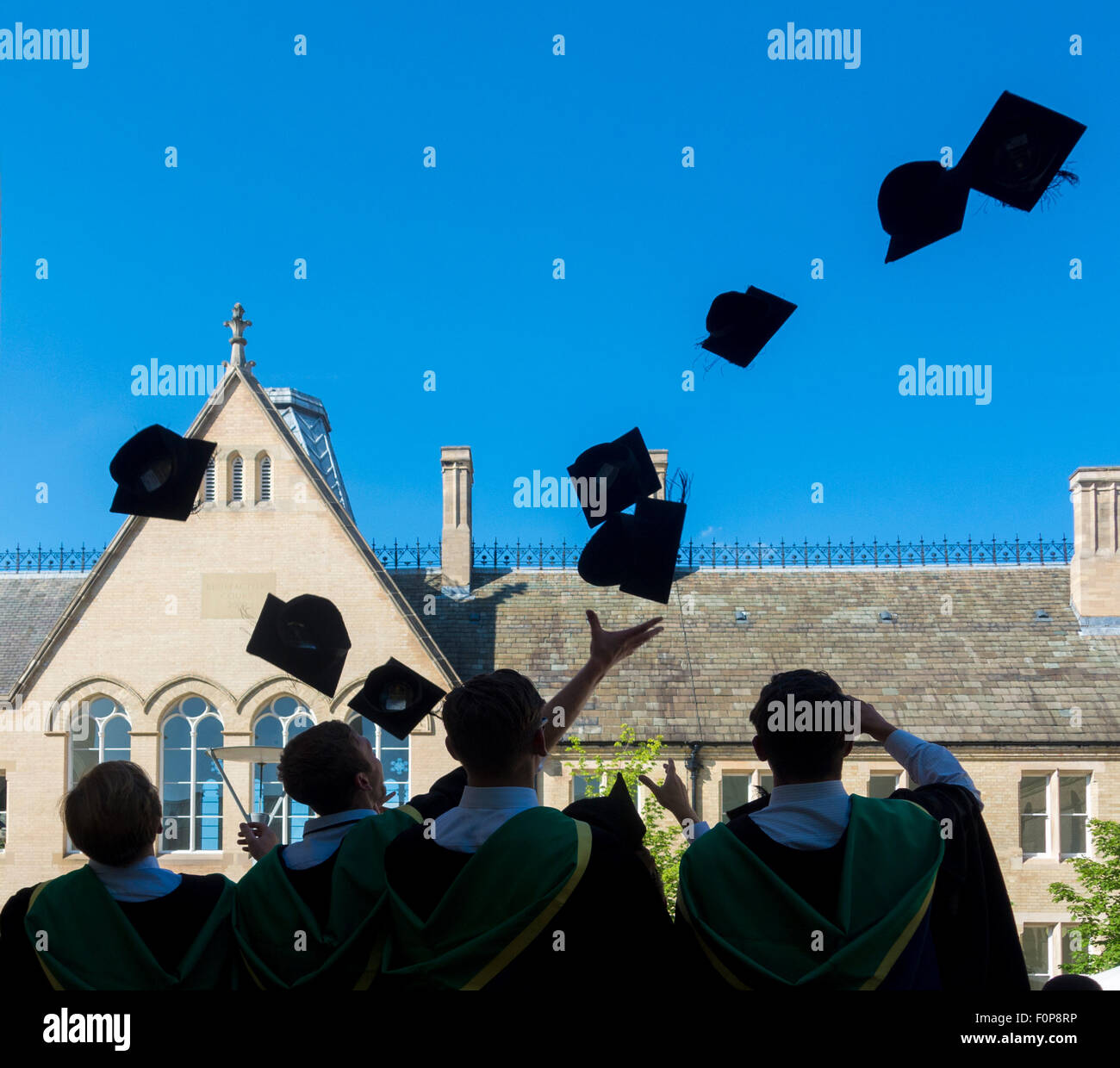 Rear view of new Graduates celebrating by throwing mortar boards in air on graduation day - Stock Image