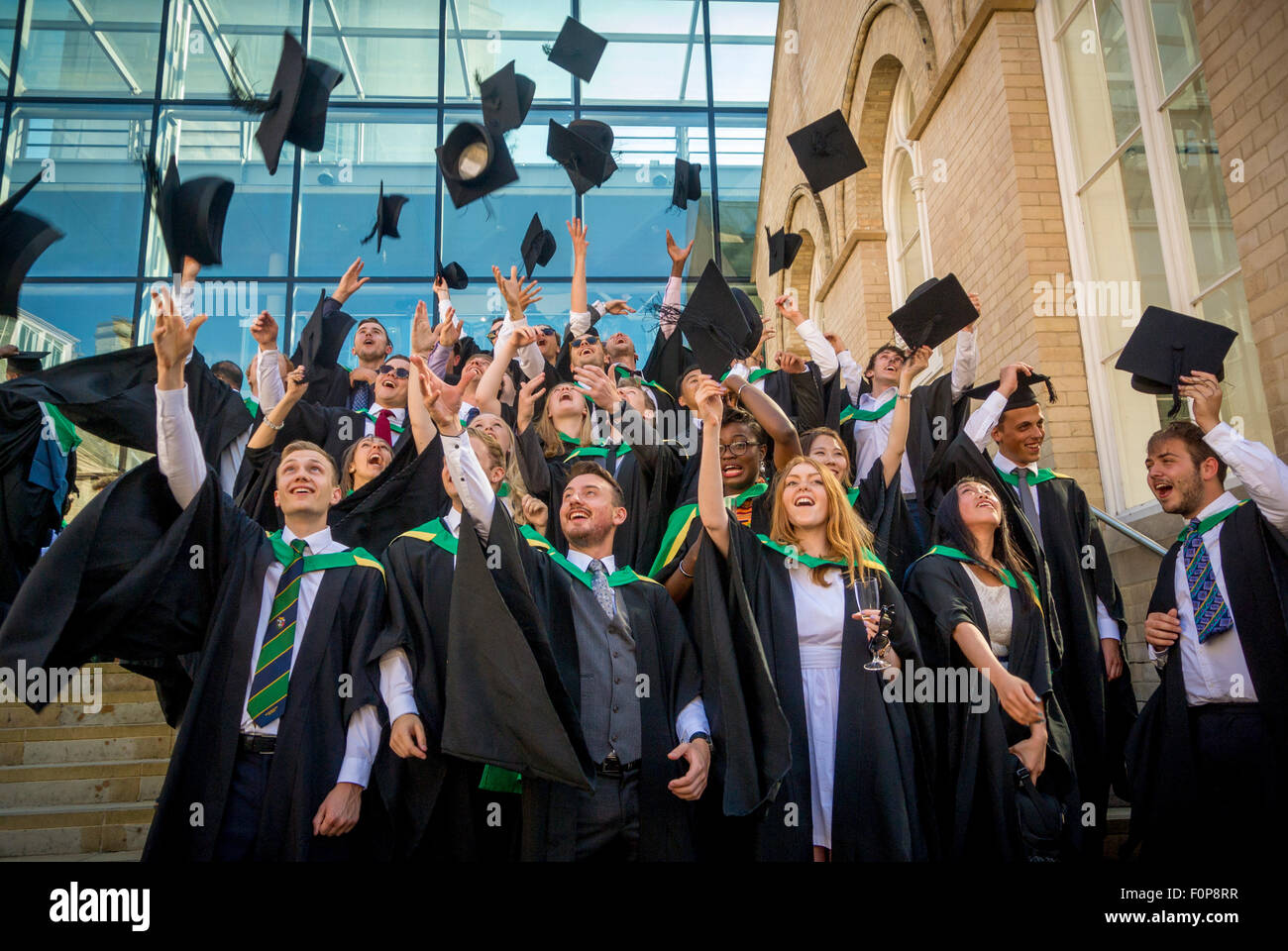 New Graduates celebrating by throwing mortar boards in air on graduation day - Stock Image