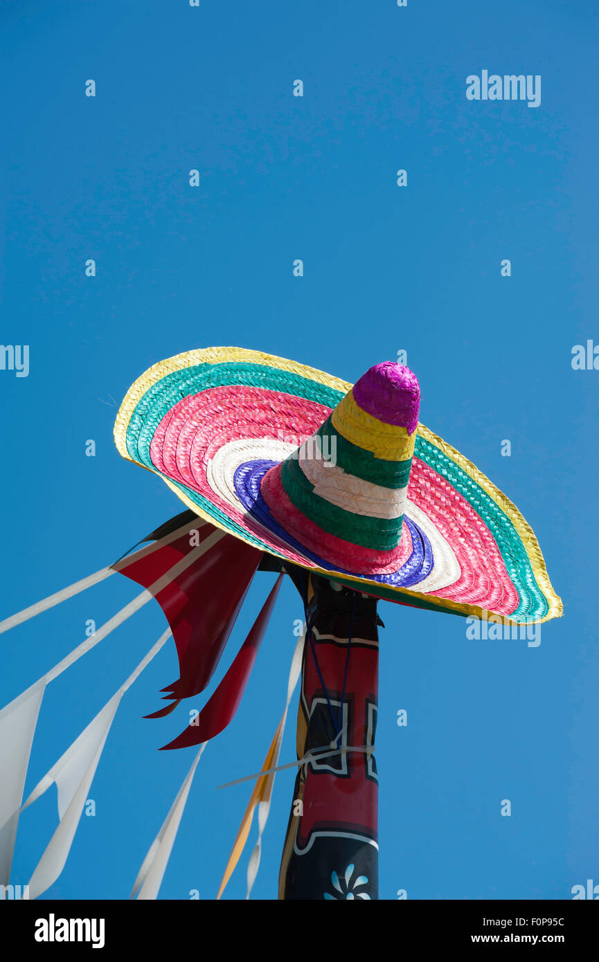 A brightly coloured sombrero perched on top of a flagpole pictured against a clear cloudless blue sky. - Stock Image