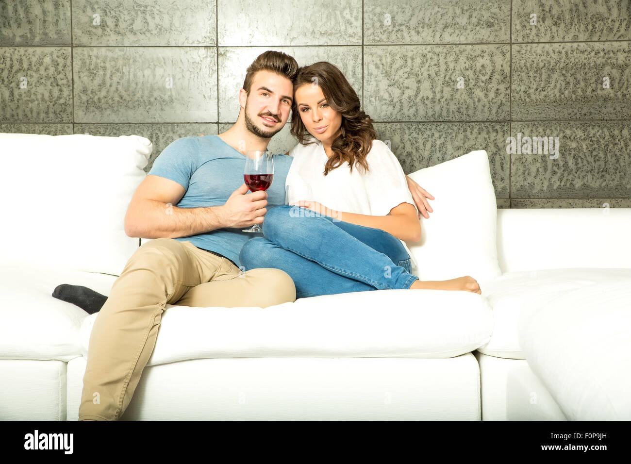 A young couple in the living room enjoying a glass of red wine on the sofa. Stock Photo