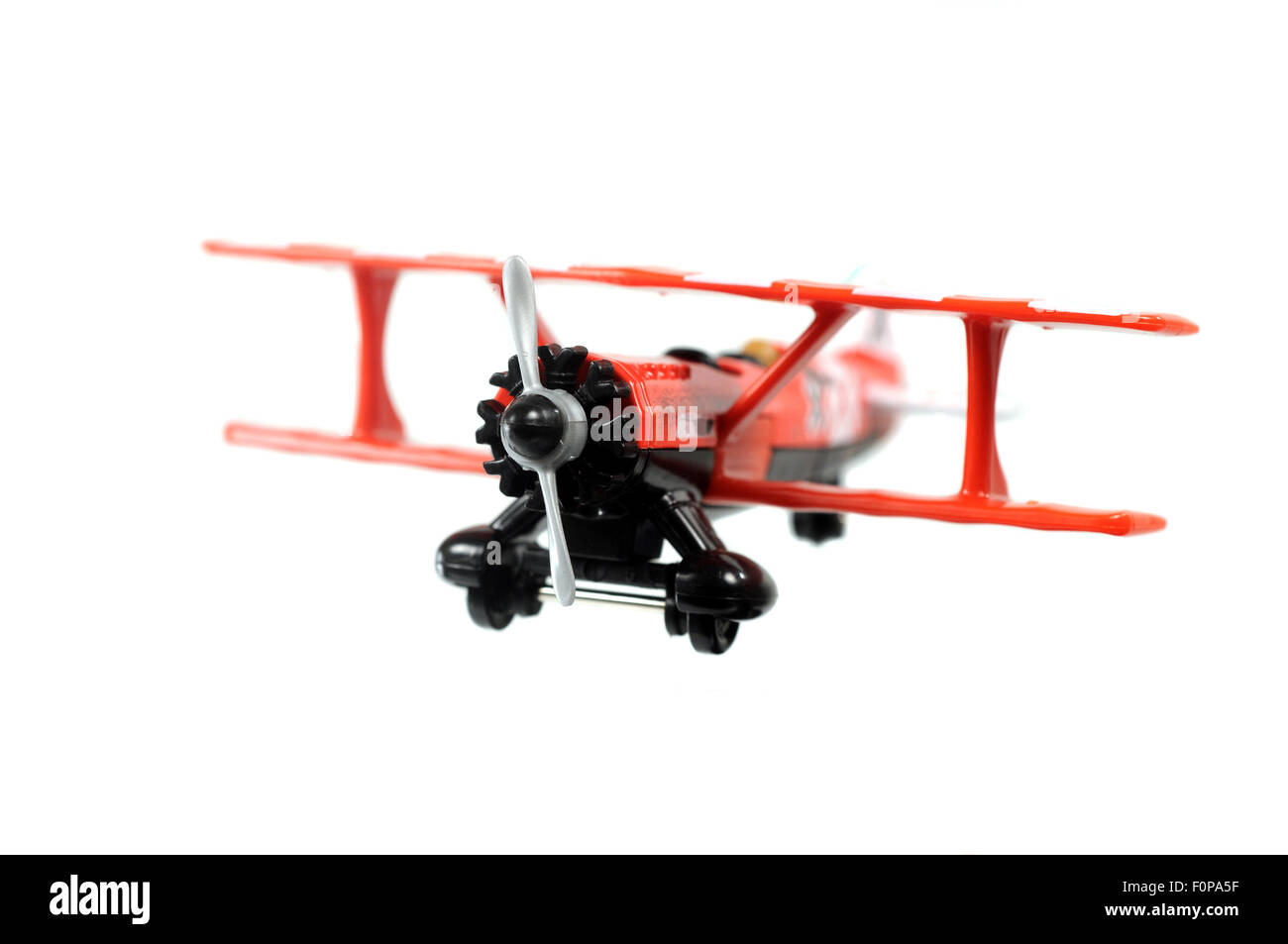 Toy red bi-plane  isolated on a white background - Stock Image
