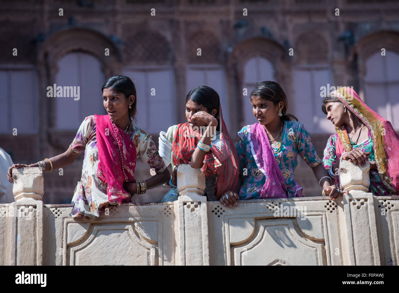 Jodhpur, India. Mehrangarh sandstone hill fort of the Marwar rulers. Four women in traditional clothes, watching. - Stock Image