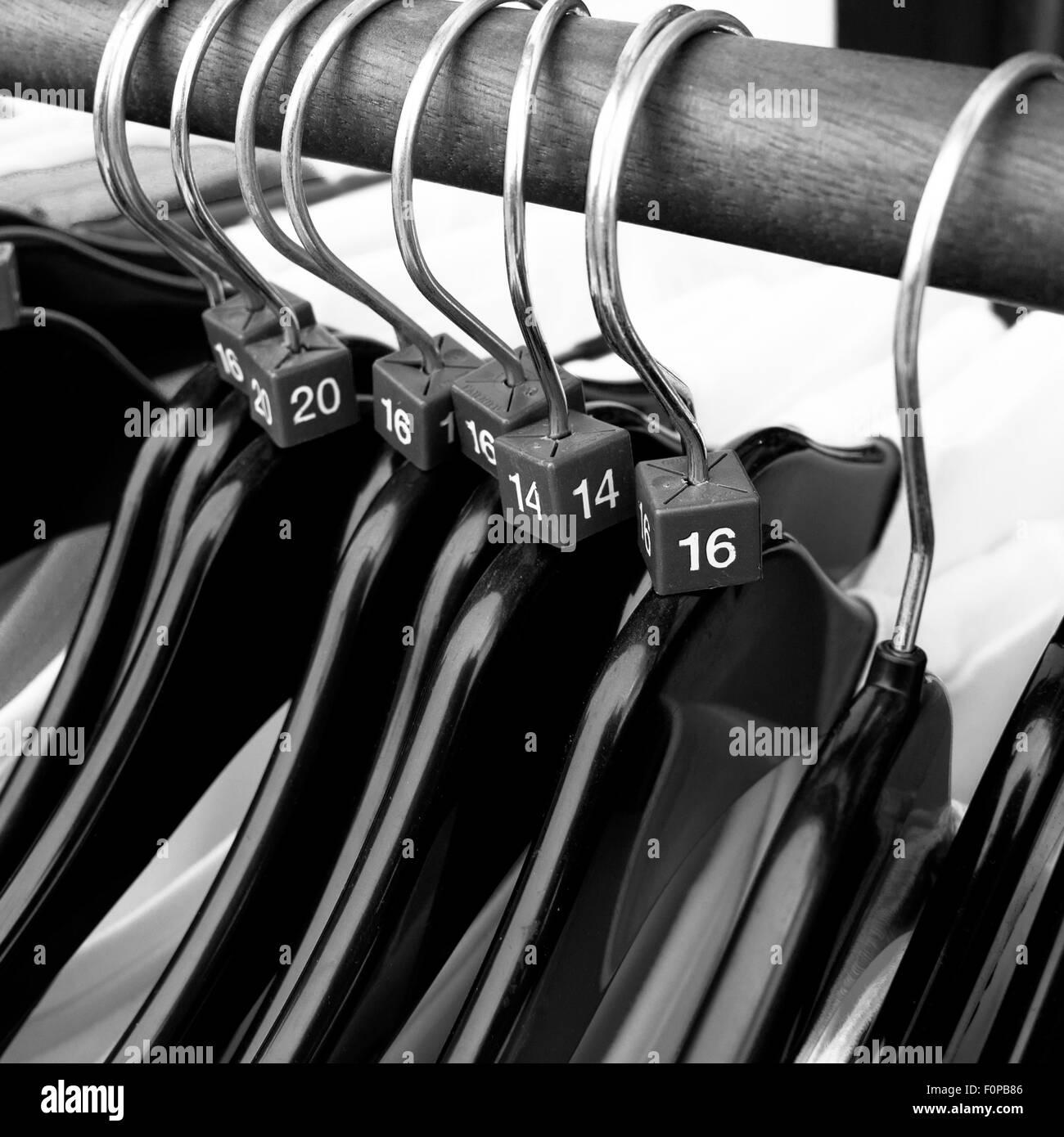 Women`s clothes sizes on coat hangers - Stock Image