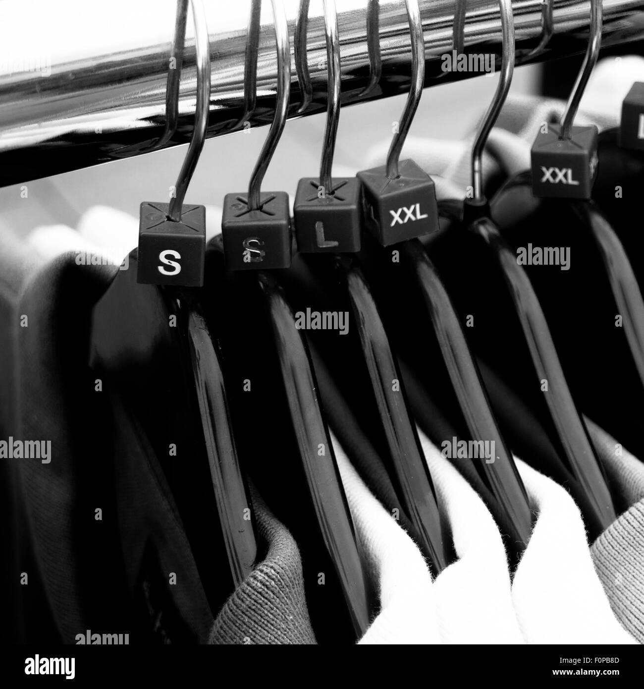 Men`s clothes sizes on coat hangers - Stock Image