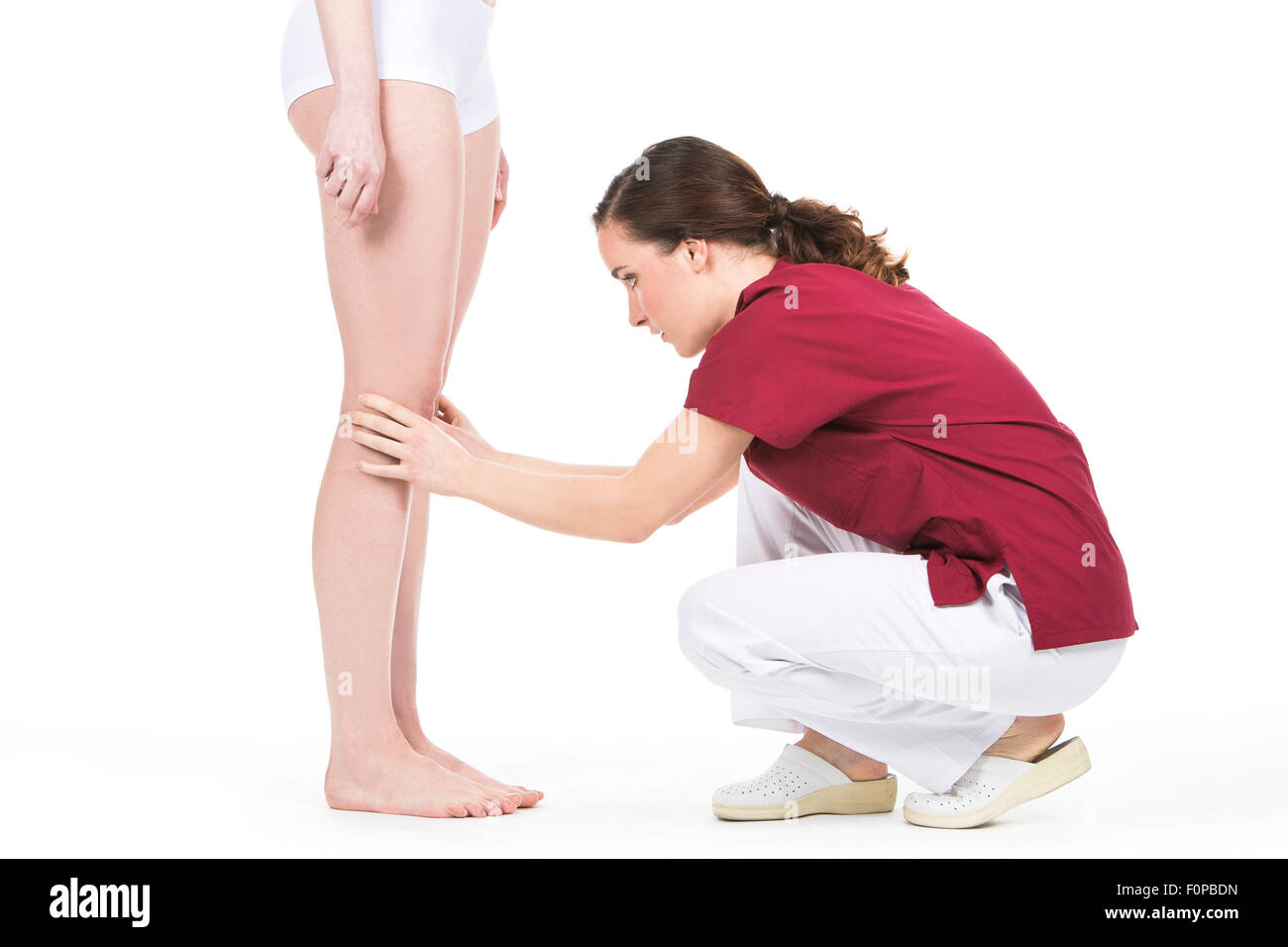 physiotherapist doing a knee evaluation to a woman patient - Stock Image