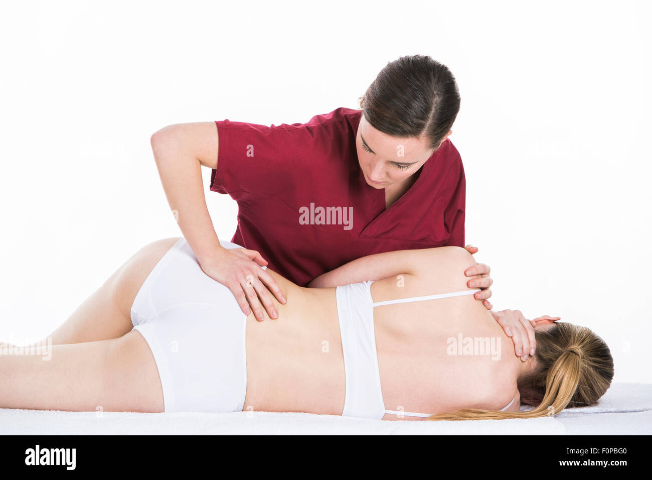 physical therapist gets spinal mobilization to a woman patient - Stock Image