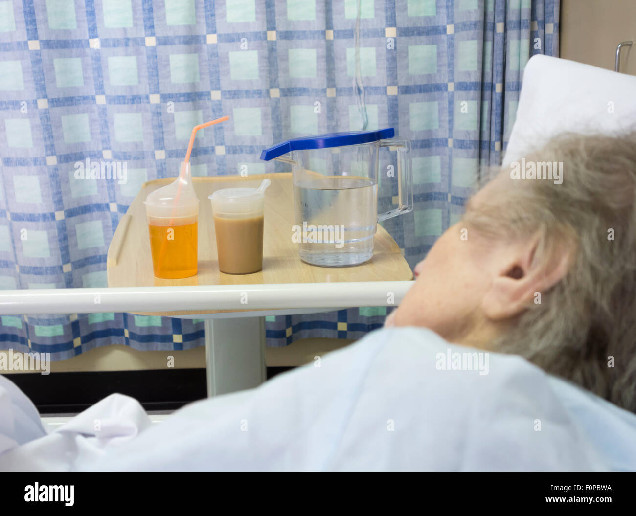 Elderly patient in her nineties in NHS hospital bed with drinks on bedside table. UK - Stock Image