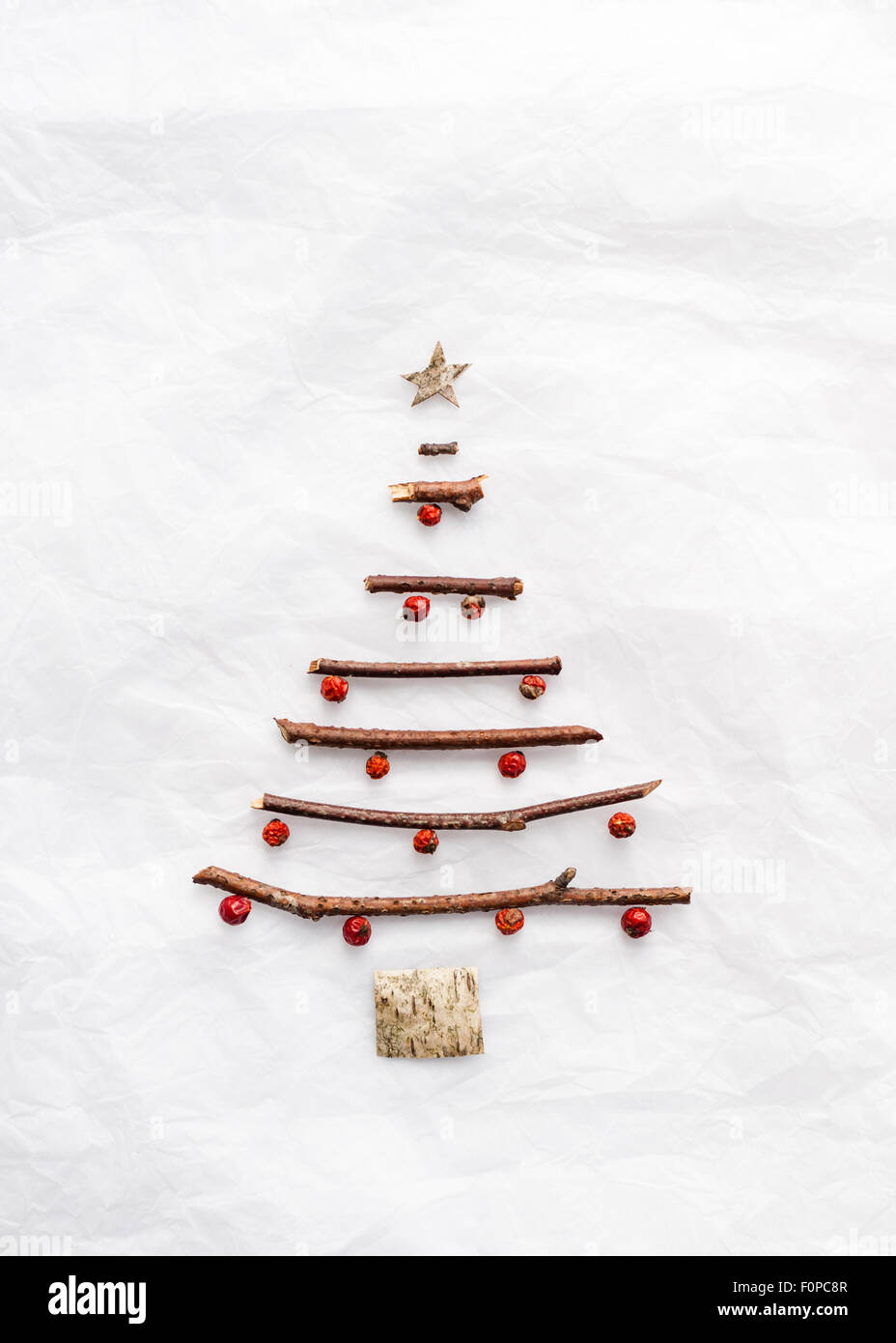 a simple christmas tree shape made with twigs birch bark and red