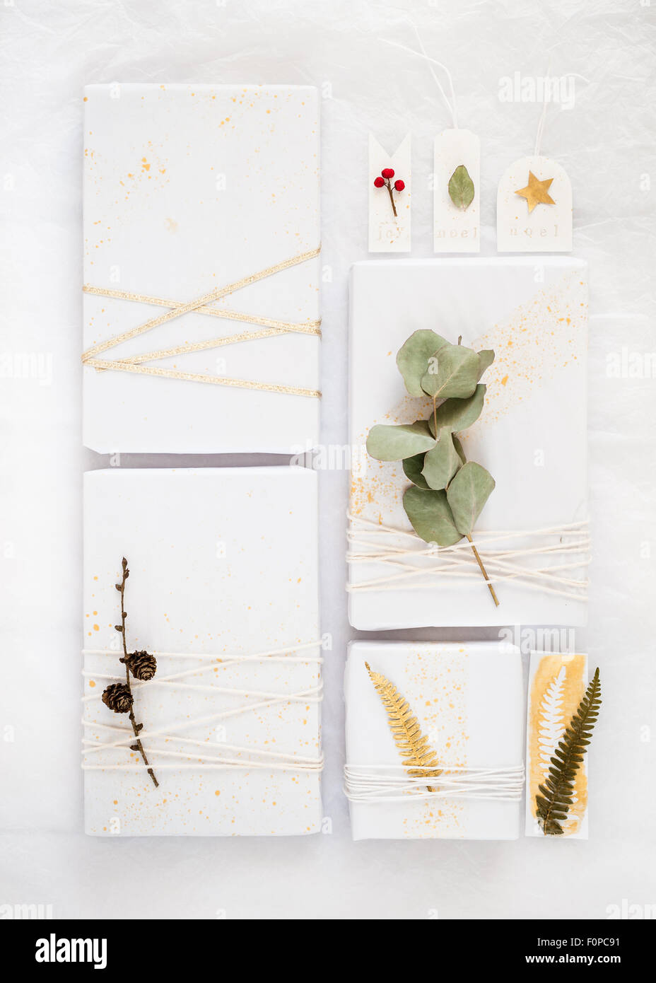 4 different creative gift wrapping ideas made with white tissue paper splattered gold paint twine ribbon and natural - Stock Image