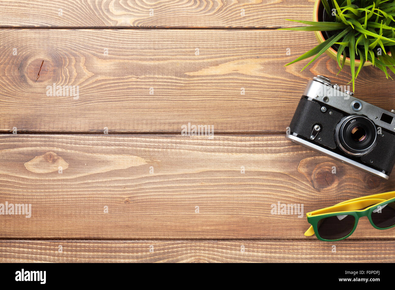 Camera, Sunglasses And Flower On Office Wooden Desk Table
