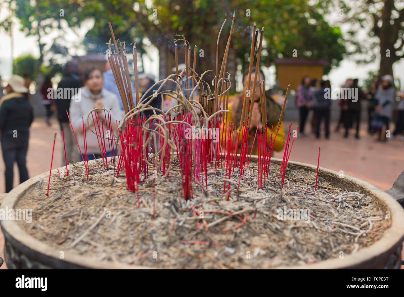 Vietnam urn incense, visitors worship before some newly planted incense sticks at the Tran Quoc Pagoda in Hanoi - Stock Image