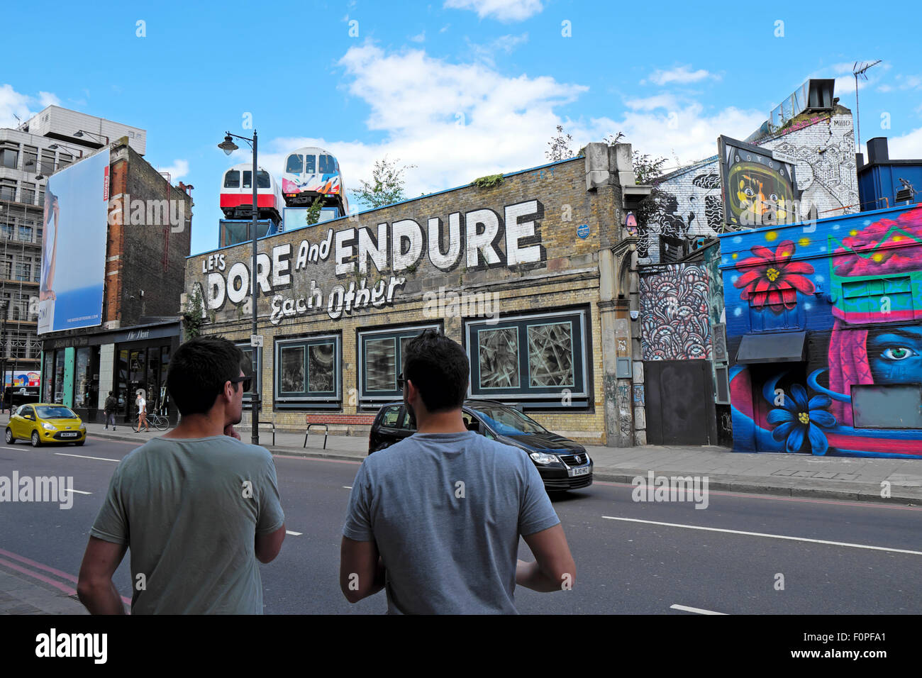 Two men looking at Let's Adore and Endure Each Other graffiti on wall in Great Eastern Street in Shoreditch - Stock Image