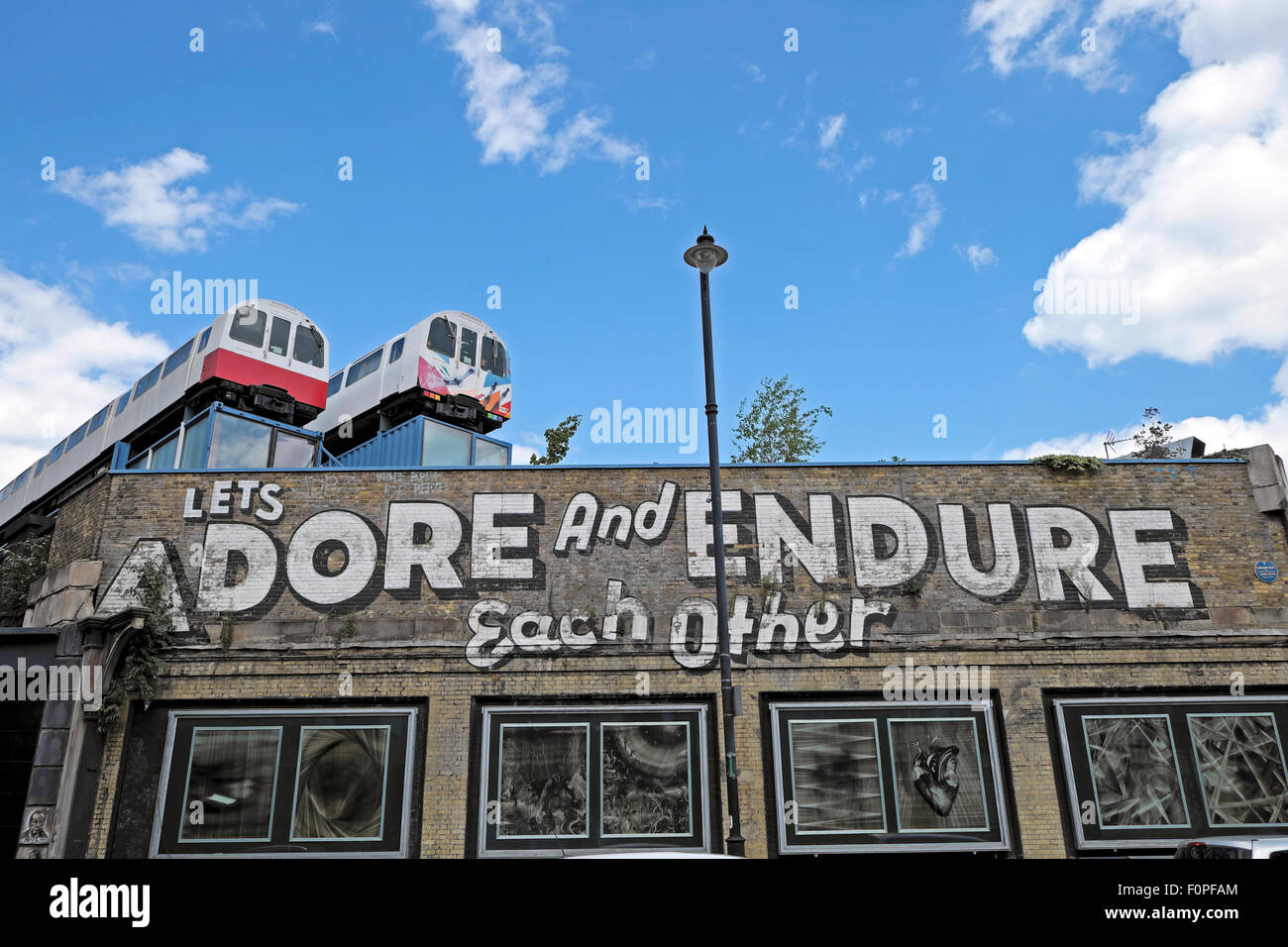 Let's Adore and Endure Each Other graffiti on wall with train carriages on a roof Great Eastern Street in Shoreditch - Stock Image