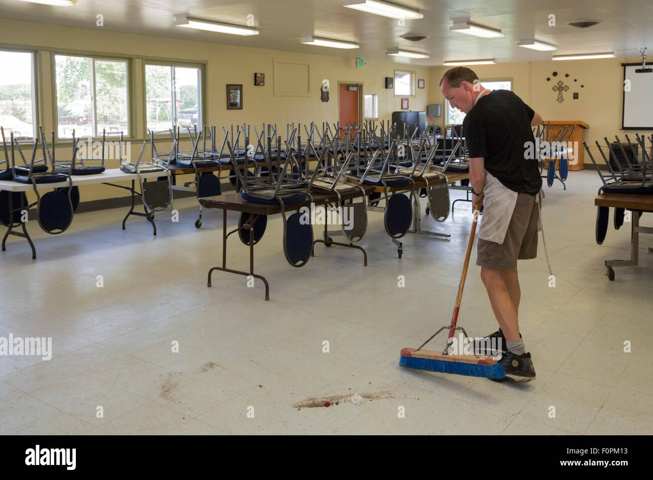 Wellington, Colorado - A resident sweeps the floor in the dining room at Harvest Farm, a addiction recovery facility. - Stock Image