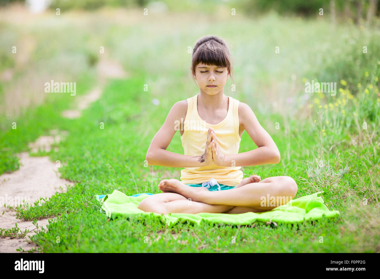 Stock Photo of Nude woman sitting in lotus position, eyes
