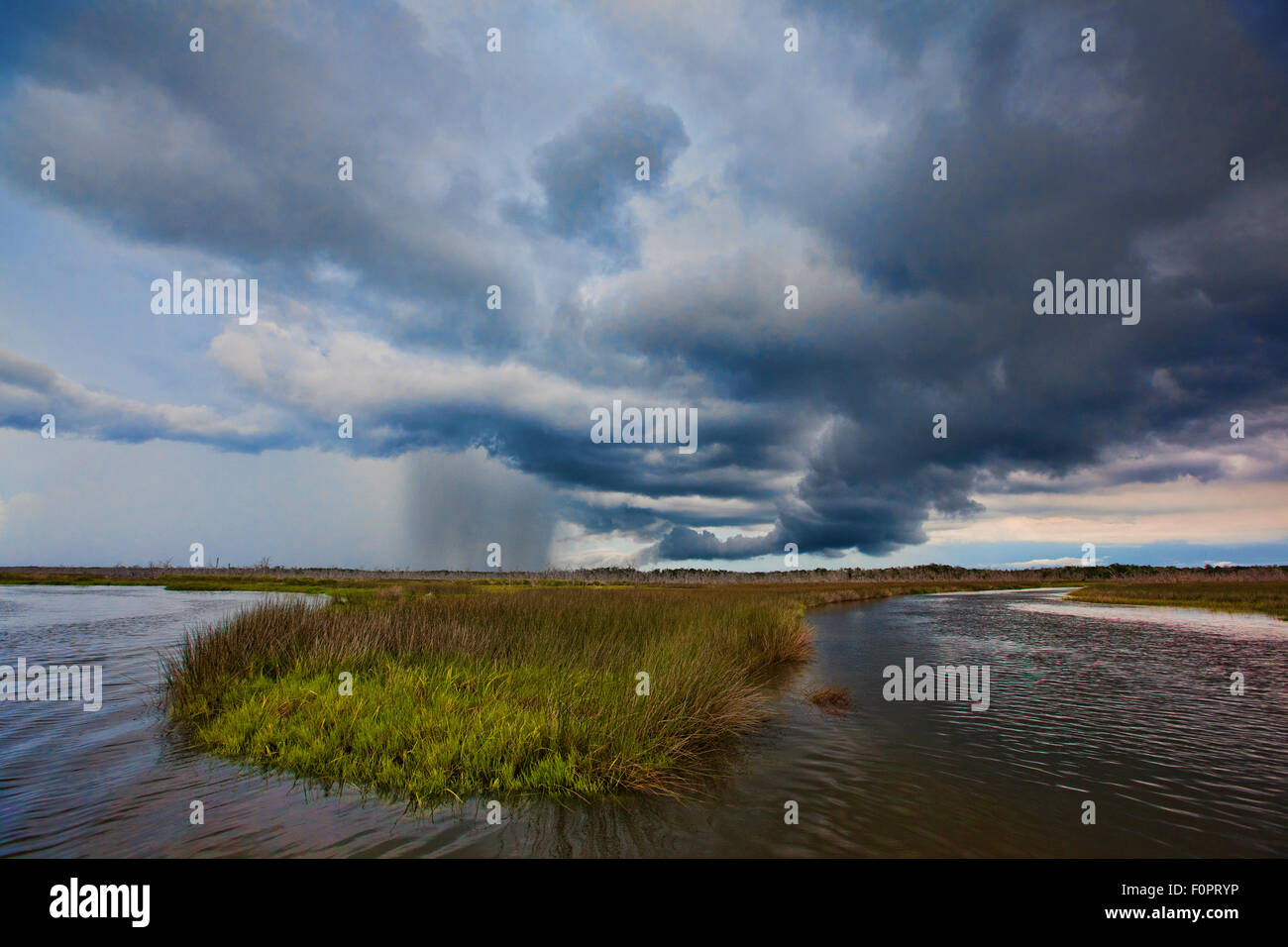 Afternoon storm clouds moving over the Central Florida Coastline along the Gulf of Mexico with rain falling Stock Photo