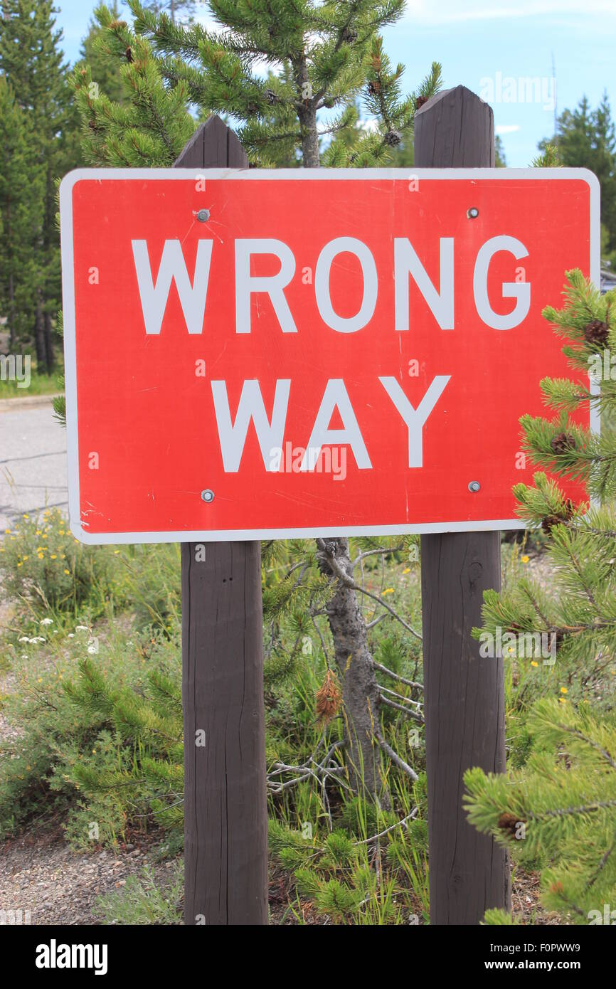 Red and white road sign stating 'WRONG WAY' informing traffic not to go down the road the wrong way - Stock Image