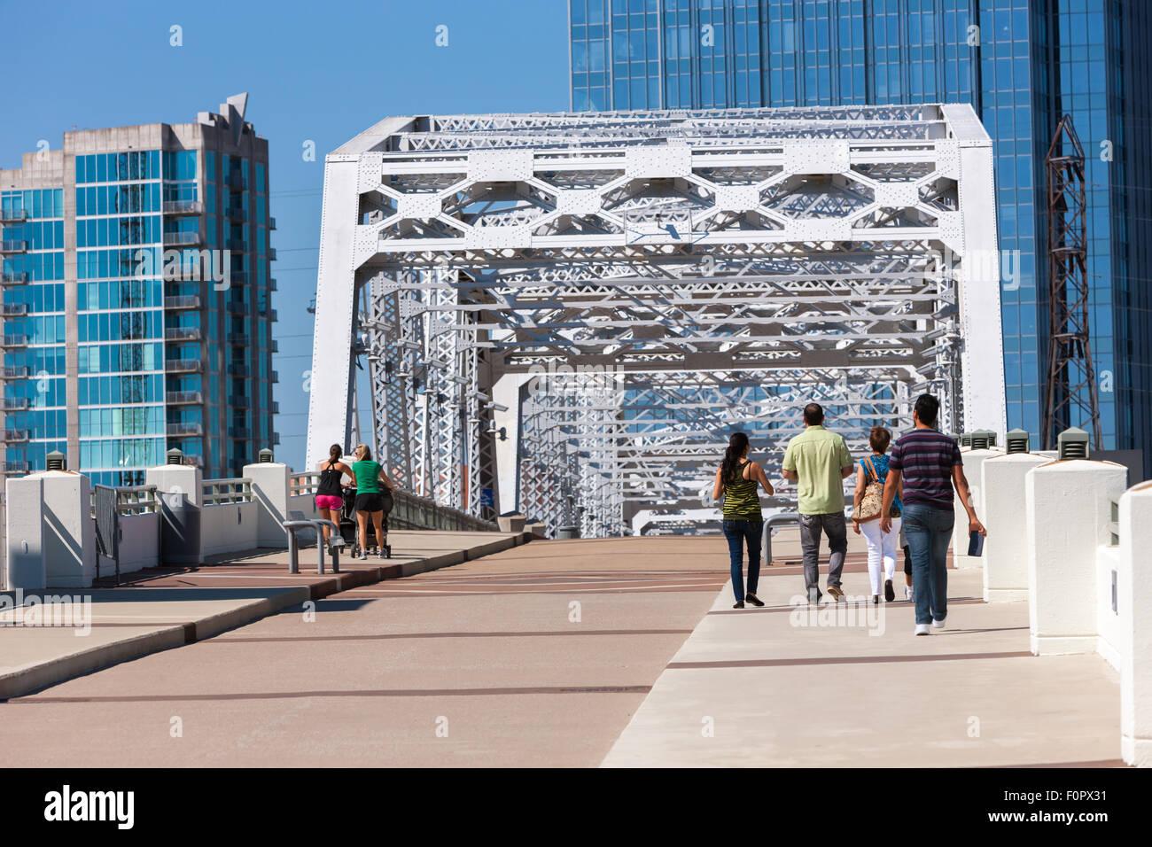 People walk across the John Seigenthaler pedestrian bridge into downtown Nashville, Tennessee. - Stock Image