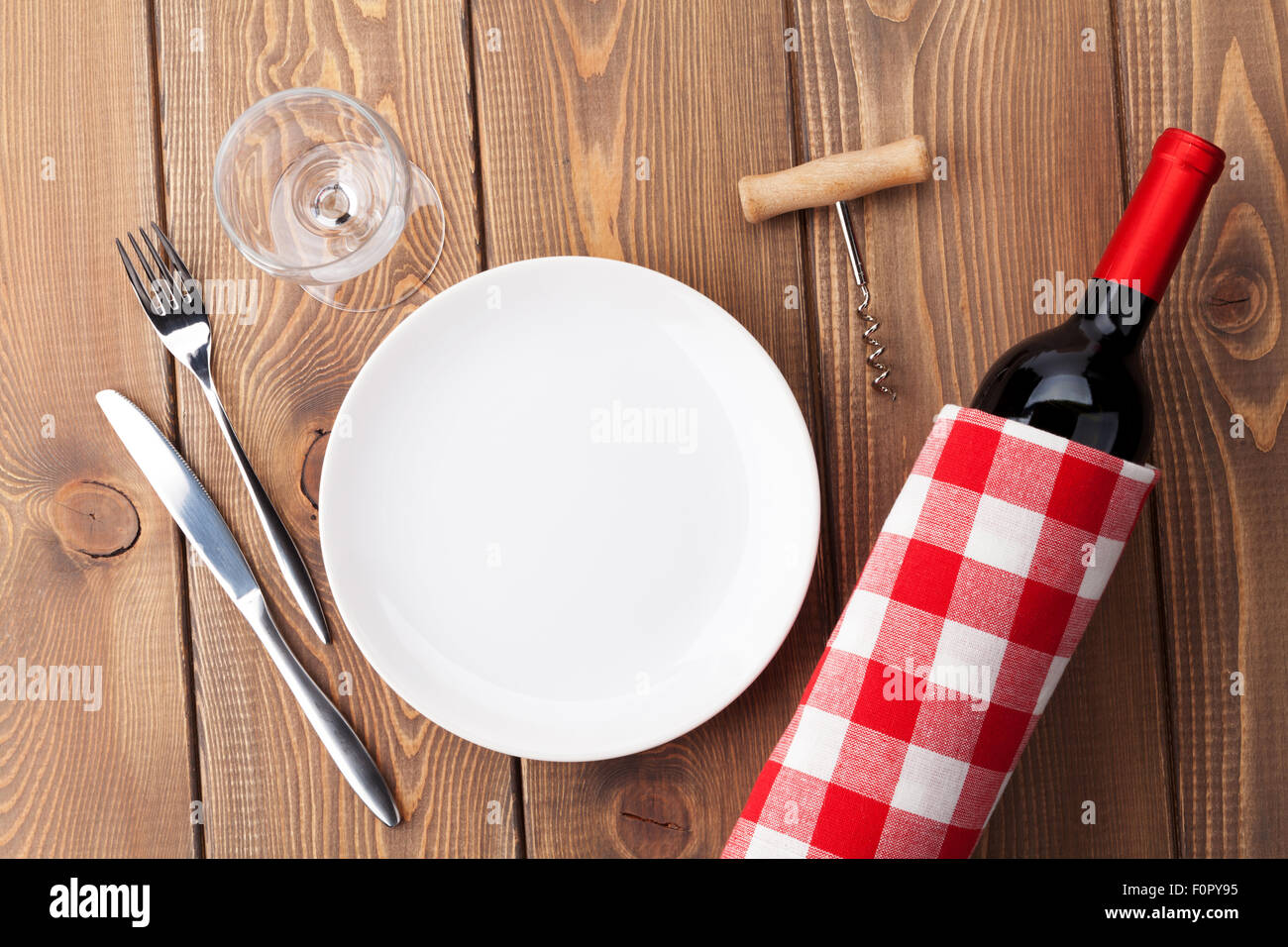 Table setting with empty plate wine glass and red wine bottle. Top view over rustic wooden table background & Table setting with empty plate wine glass and red wine bottle. Top ...