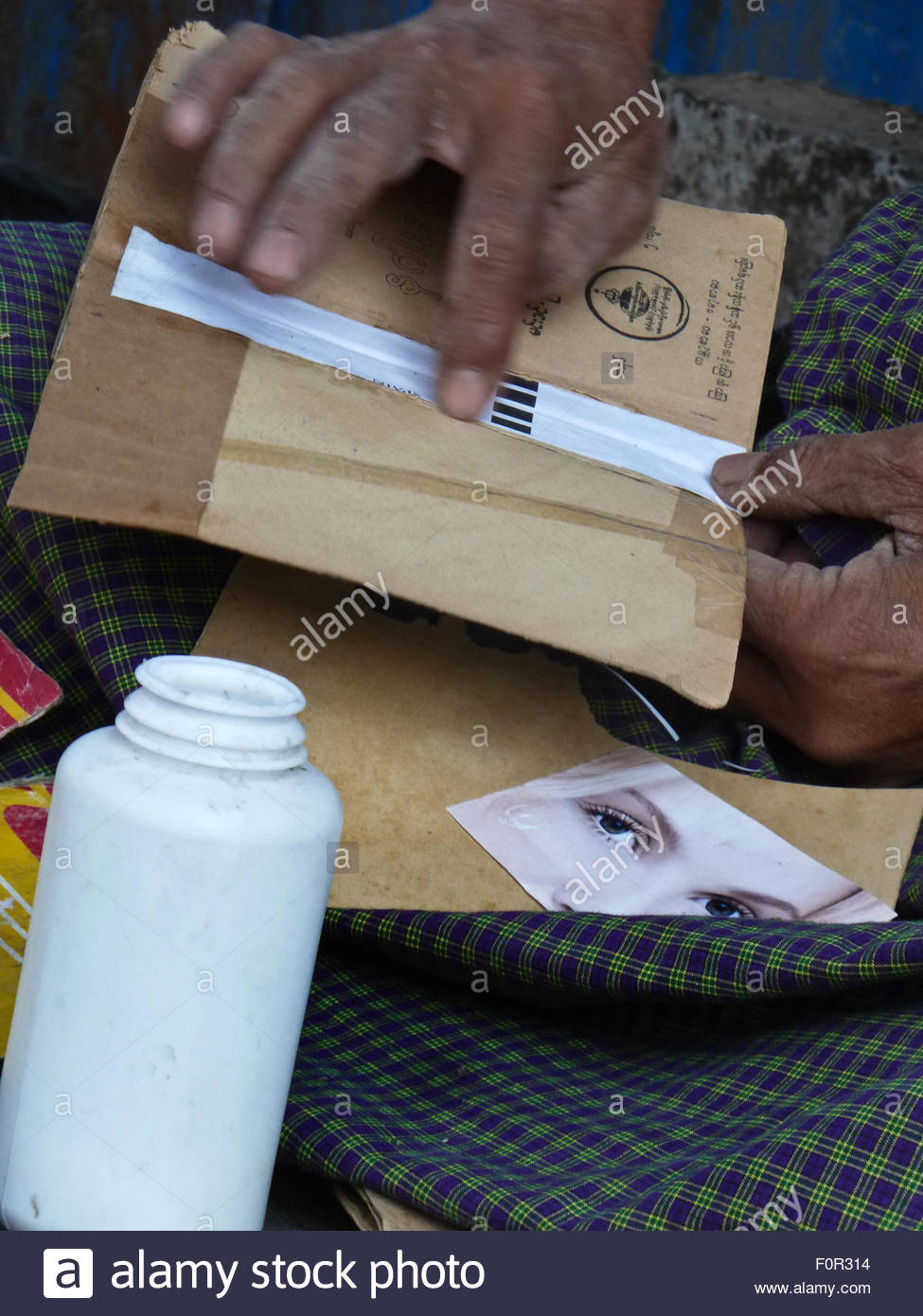 Close up hands and glue bottle of a sidewalk bookseller repairing a book at his table in Yangon, Myanmar where he - Stock Image