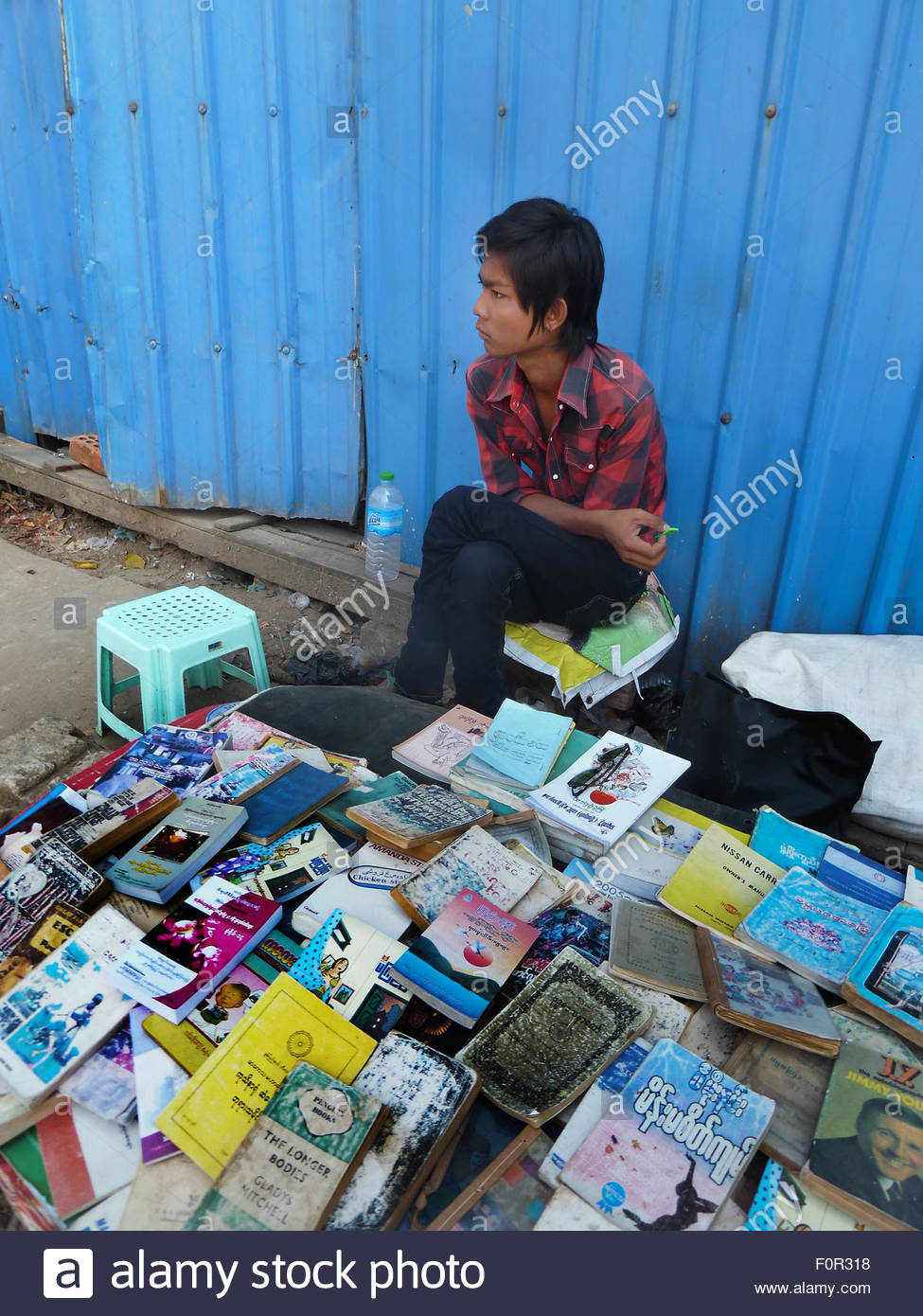View of a youthful sidewalk bookseller at his table in Yangon, Myanmar where he sells used and second hand books - Stock Image