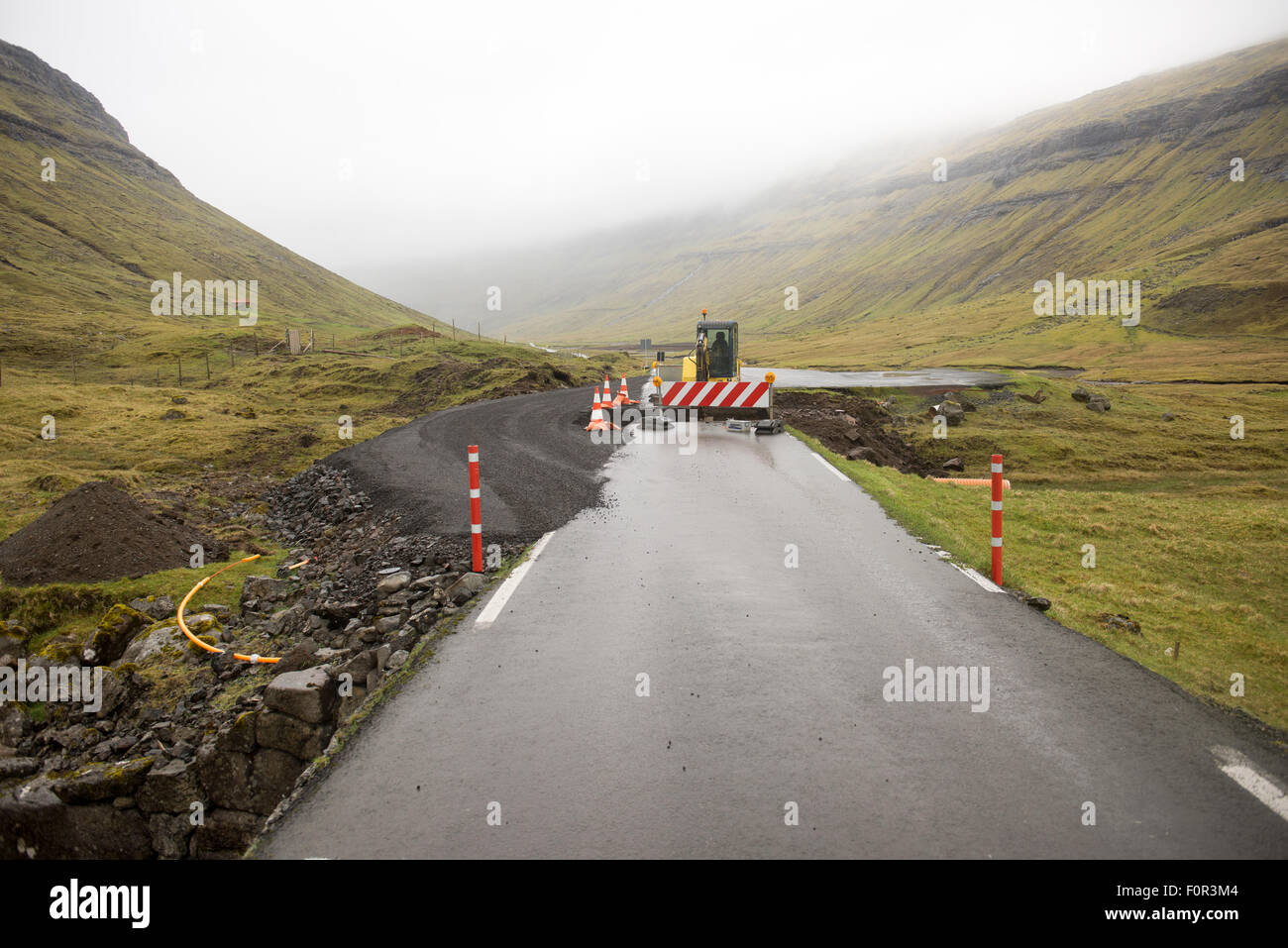 Road construction site on the Faroe Islands with road block sign and digger - Stock Image