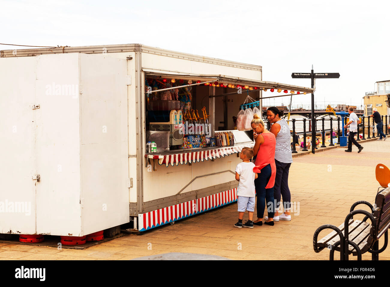 Sweet shack on Cleethorpes promenade selling slush drinks and candy floss to kids children child boy buying - Stock Image
