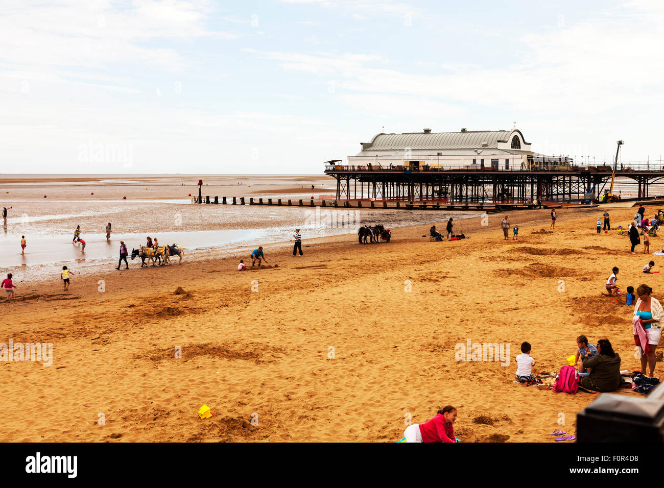 Cleethorpes seafront beach kids playing in sand in front of the pier UK town towns England coast coastal sea - Stock Image