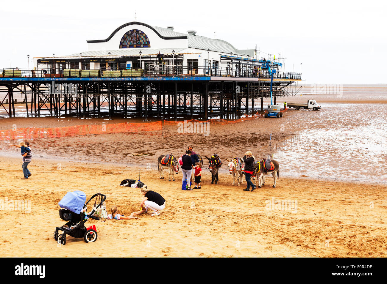 Cleethorpes pier Donkey ride rides on beach child sat on riding donkeys summer entertainment for kids UK England - Stock Image