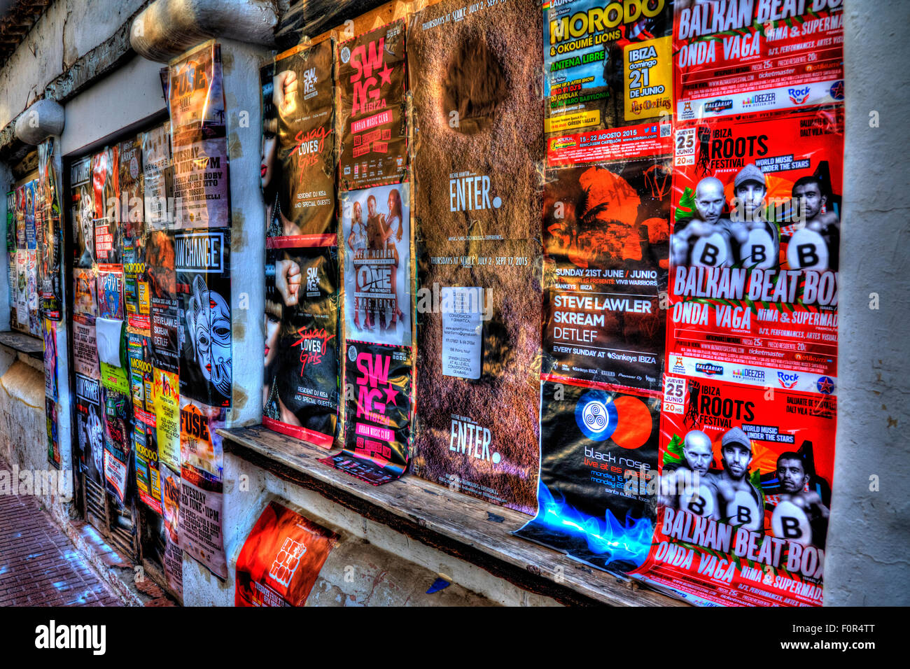 posters stuck on wall advertising bill posting adverts Ibiza clubs concerts events advertised bill posters adverts - Stock Image