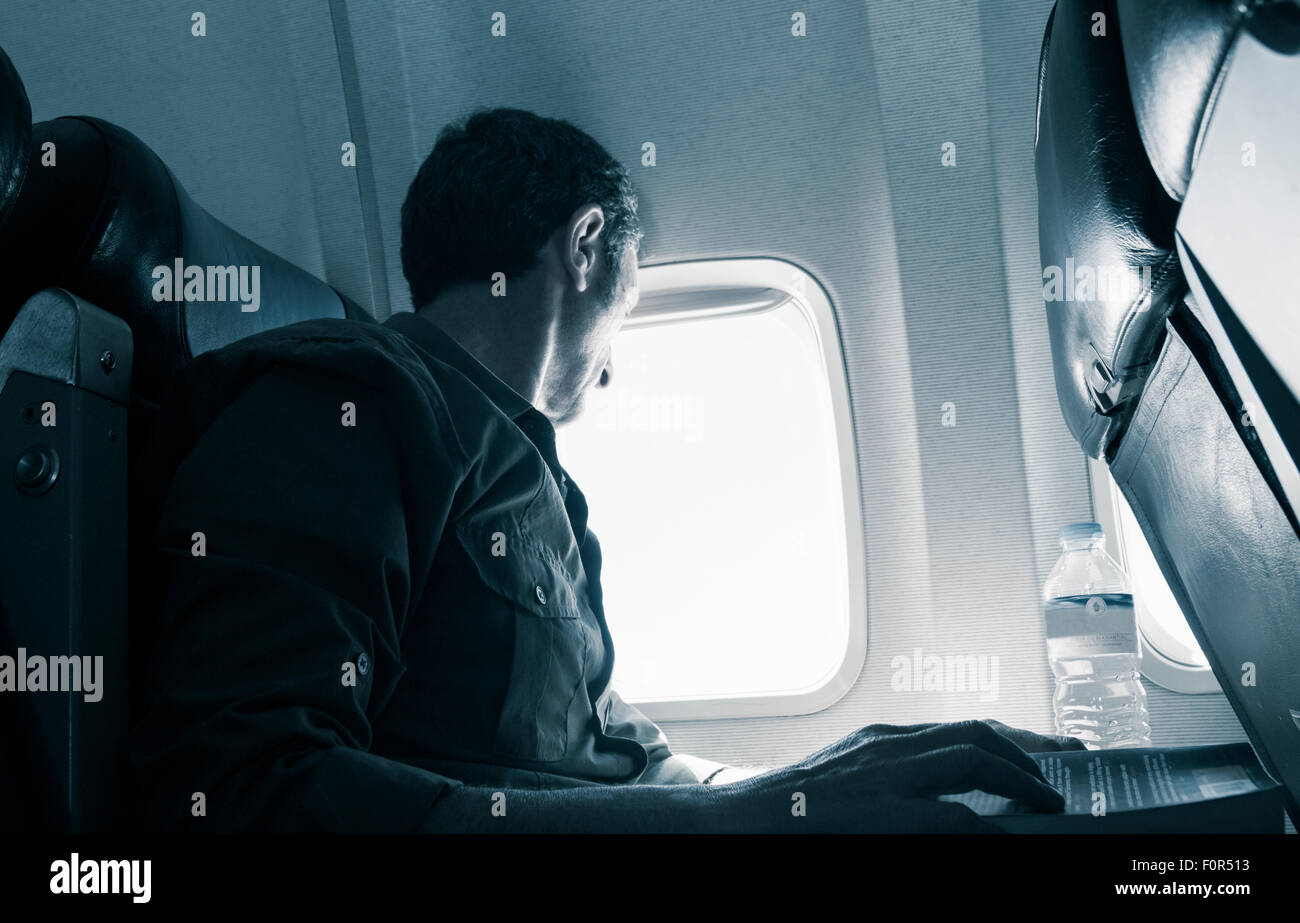Mature man sitting in window seat on airplane. - Stock Image