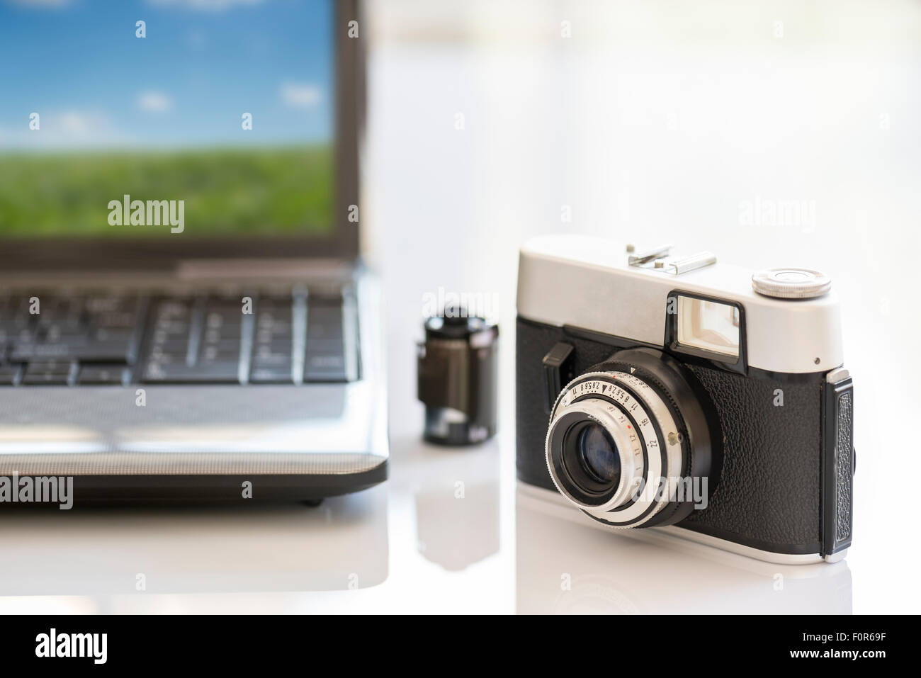35mm vintage photocamera on white table near notebook and film Stock Photo