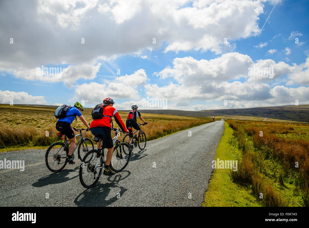 Cyclists on road across the Bowland Fells Lancashire which has its high point at Cross o'Greet - Stock Image